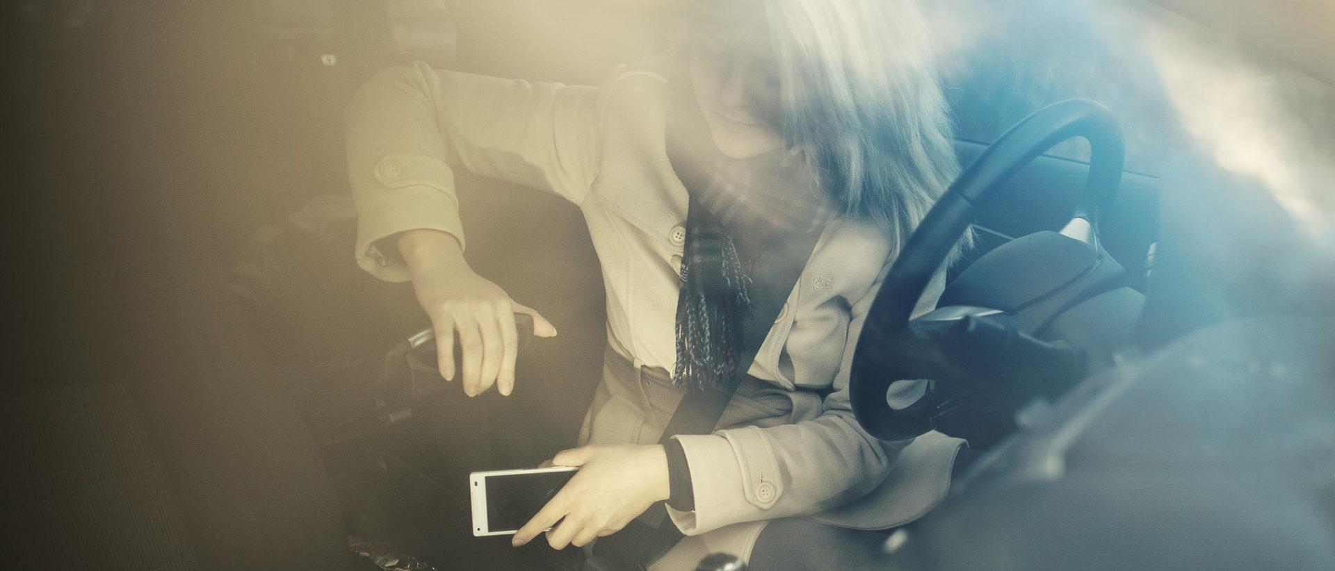 Kuvassa autoilija laittaa kännykän pois ajon ajaksi