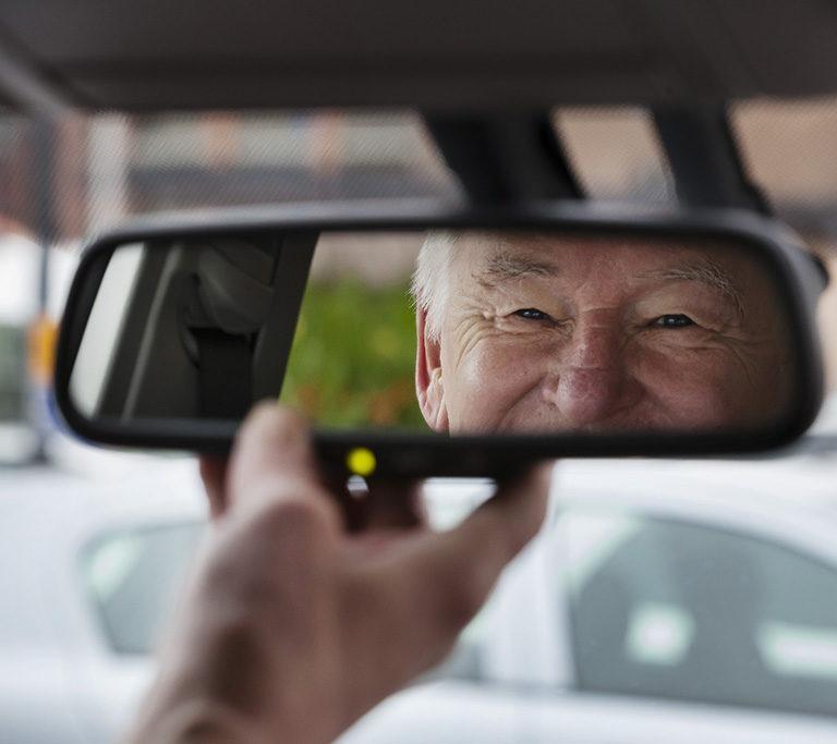 Kuvassa iäkäs henkilö auton ratissa
