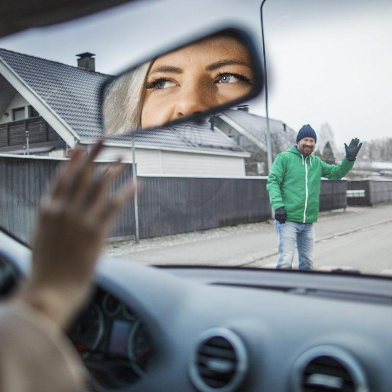 Kuvassa autoilija tervehtii jalankulkijaa