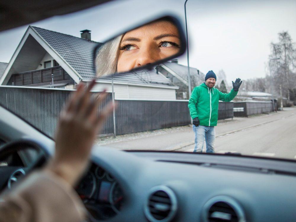 Kuvassa autoilija tervehtii kävelijää