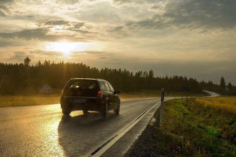 Kuvassa auto auringonlaskussa