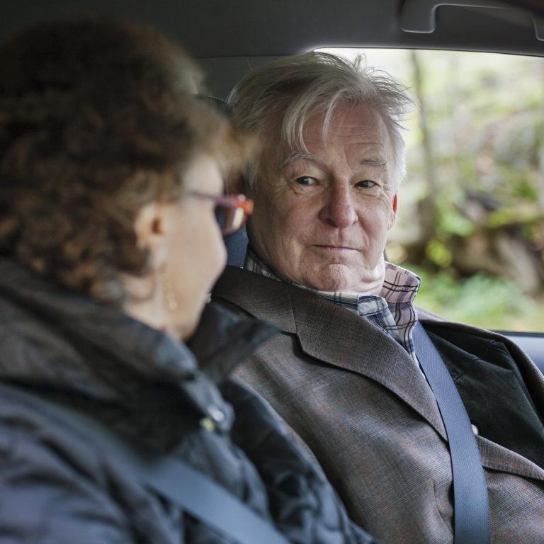 Kuvassa iäkäs henkilö ratissa