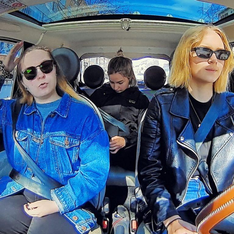 Kuvassa kolme naista matkustaa autolla. Takapenkillä turvavyö on vedetty väärin.
