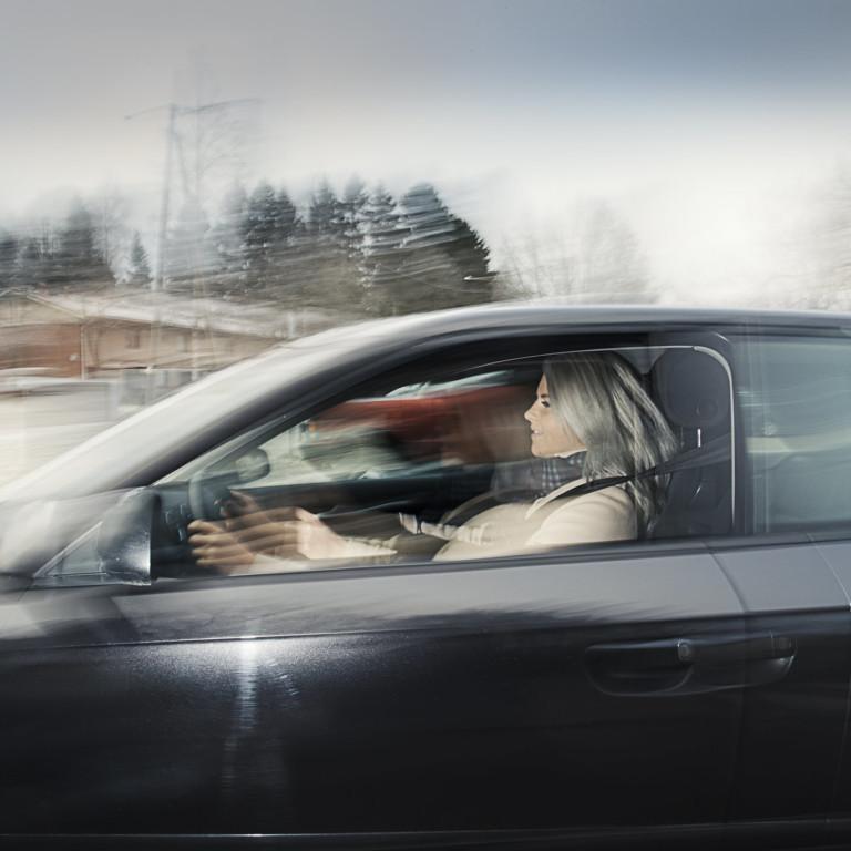 Kuvassa nainen autoilee.