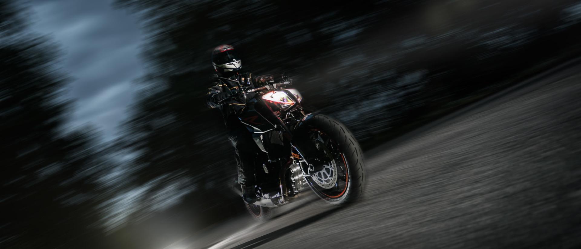 Kuvassa motoristi tiellä pimeällä