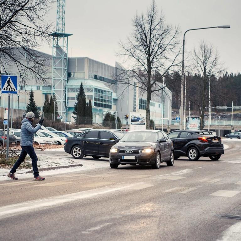 Kuvassa mies ylittää suojatien, autoilija antaa tietä.
