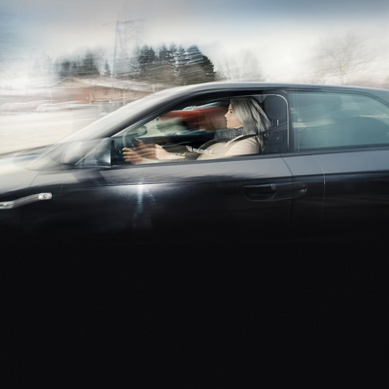 Kuvassa tummaa autoa ajava kuljettaja.