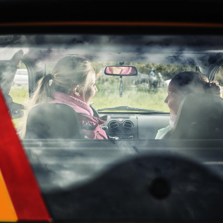 Kuvassa kaksi nuorta istuu mopoautossa.