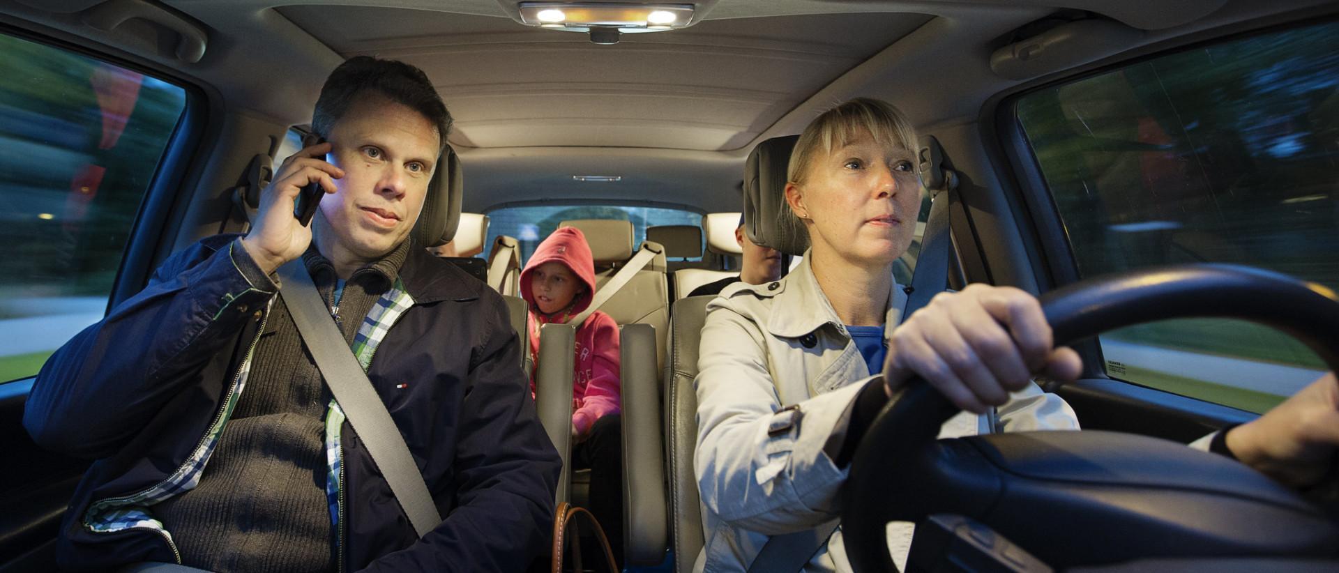 Kuvassa apukuljettaja autossa puhuu puhelimeen kuljettajan keskittyessä ajamiseen.