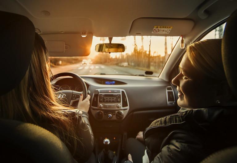 Kuvassa nuori kuljettaja autossa vanhempansa kanssa.
