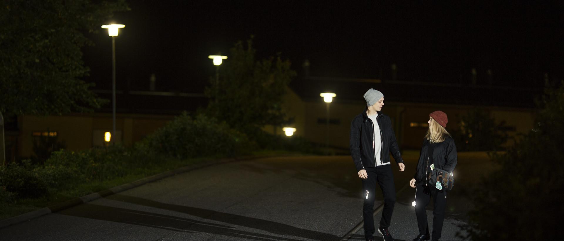 Kuvassa kaksi nuorta heijastimin varustautunutta jalankulkijaa
