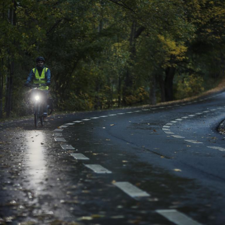 Kuvassa pyöräilijä pimeällä tiellä ajaa etuvalo palaen.