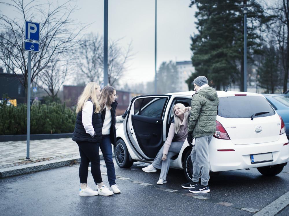 Kuvassa neljä nuorta ihmistä juttelee auton luona.