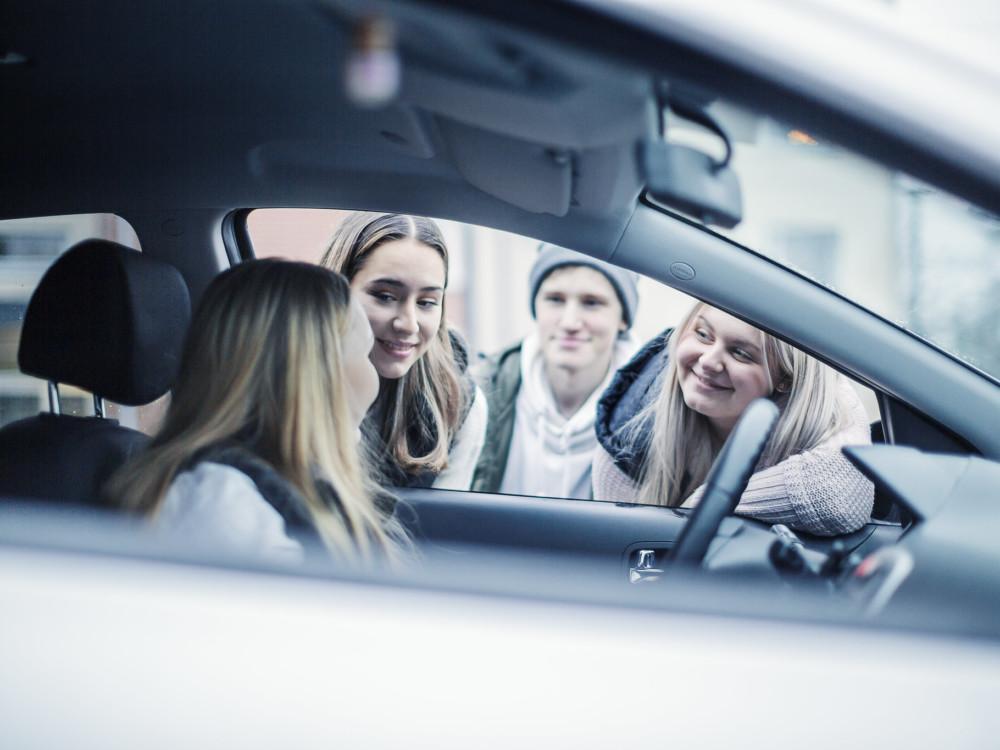 Kuvassa nuori kuljettaja pysähtyneessä henkilöautossa, muita nuoria juttelee hänelle ikkunan kautta.