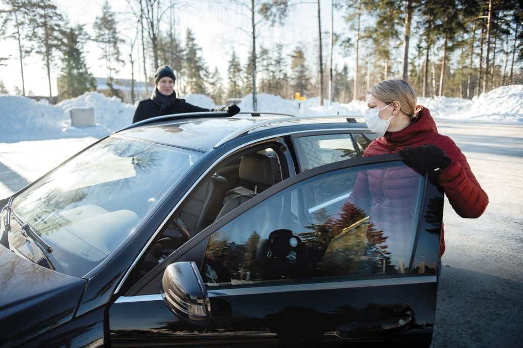 Kuljettaja ja matkustaja menossa autoon.
